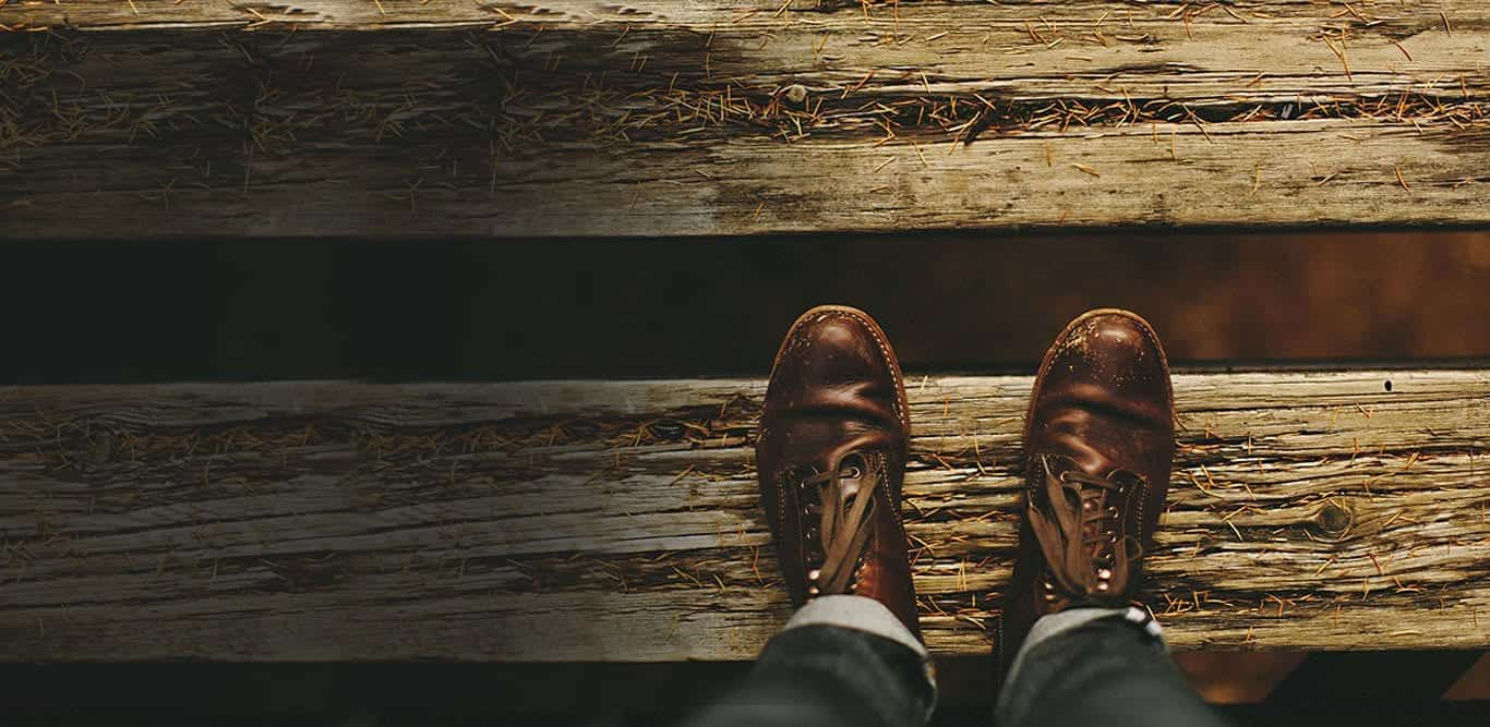 Looking down at brown shoes standing on worn planks of wood