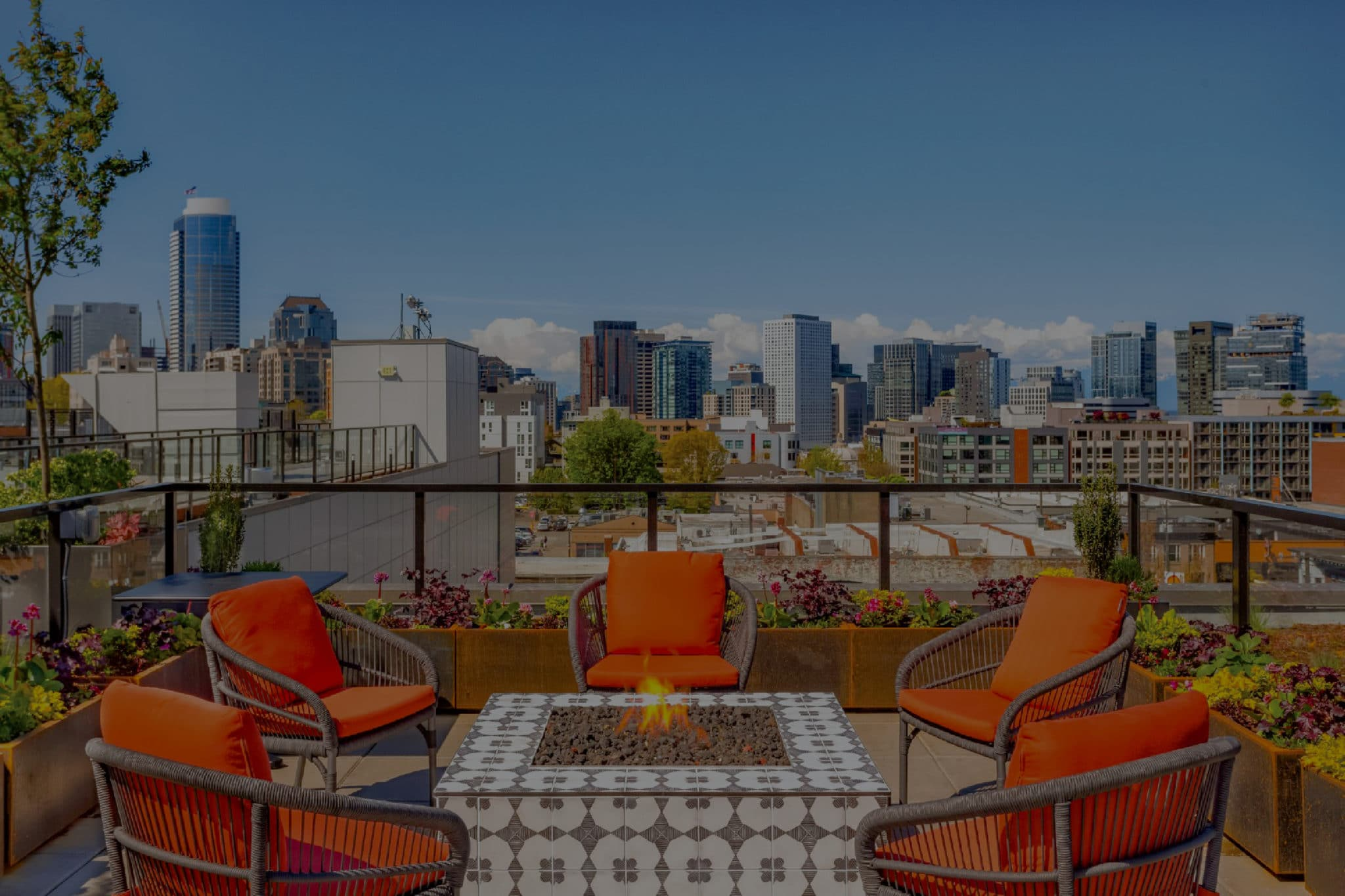 Rooftop Patio with a fireplace and bright orange chairs.