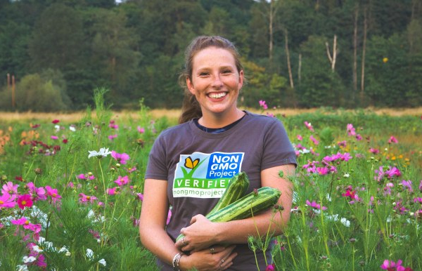 non-gmo project worker in field of flowers holding squash