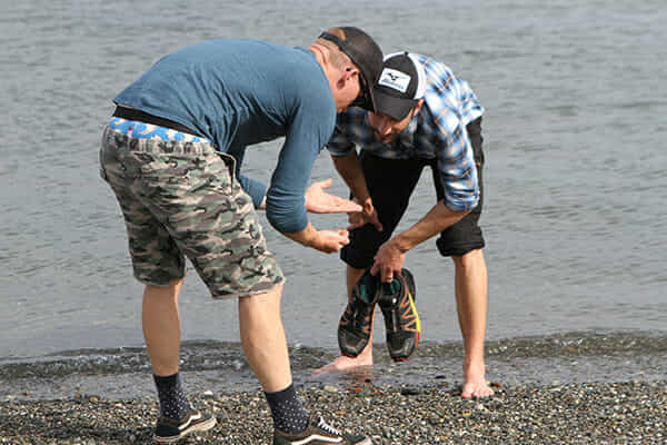 Two men looking at rocks on the beach in Washington