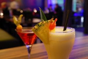 A cocktail close-up, a wedge of pineapple garnishes the rim.
