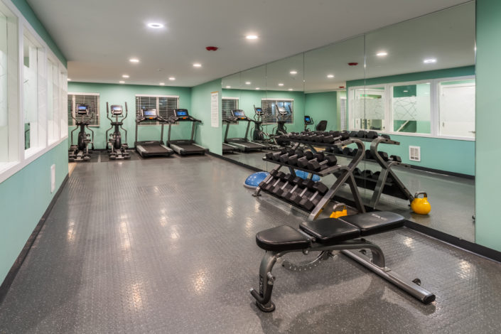 A fitness room with weights and machines.
