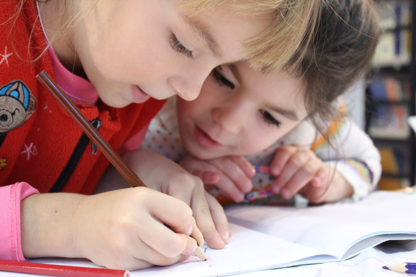 two elementary school children writing in a journal together