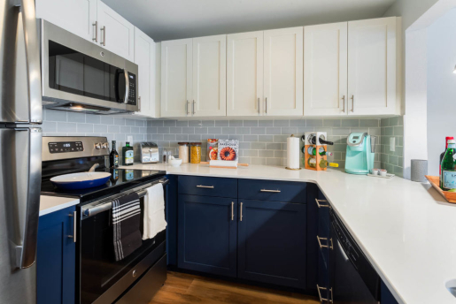 kitchen with stainless steel oven and fridge, gray brick tile,white and blue color scheme