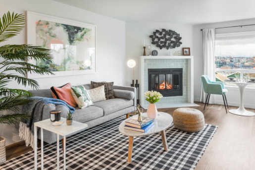 living room with fireplace, window overlooking Seattle, furnished with modern art, throw pillows, and plants