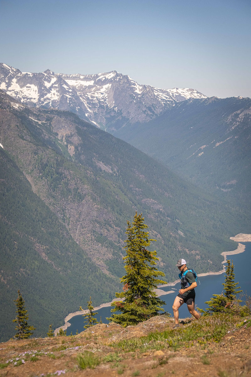 A man trail running in front of Ross Lake in the North Cascades