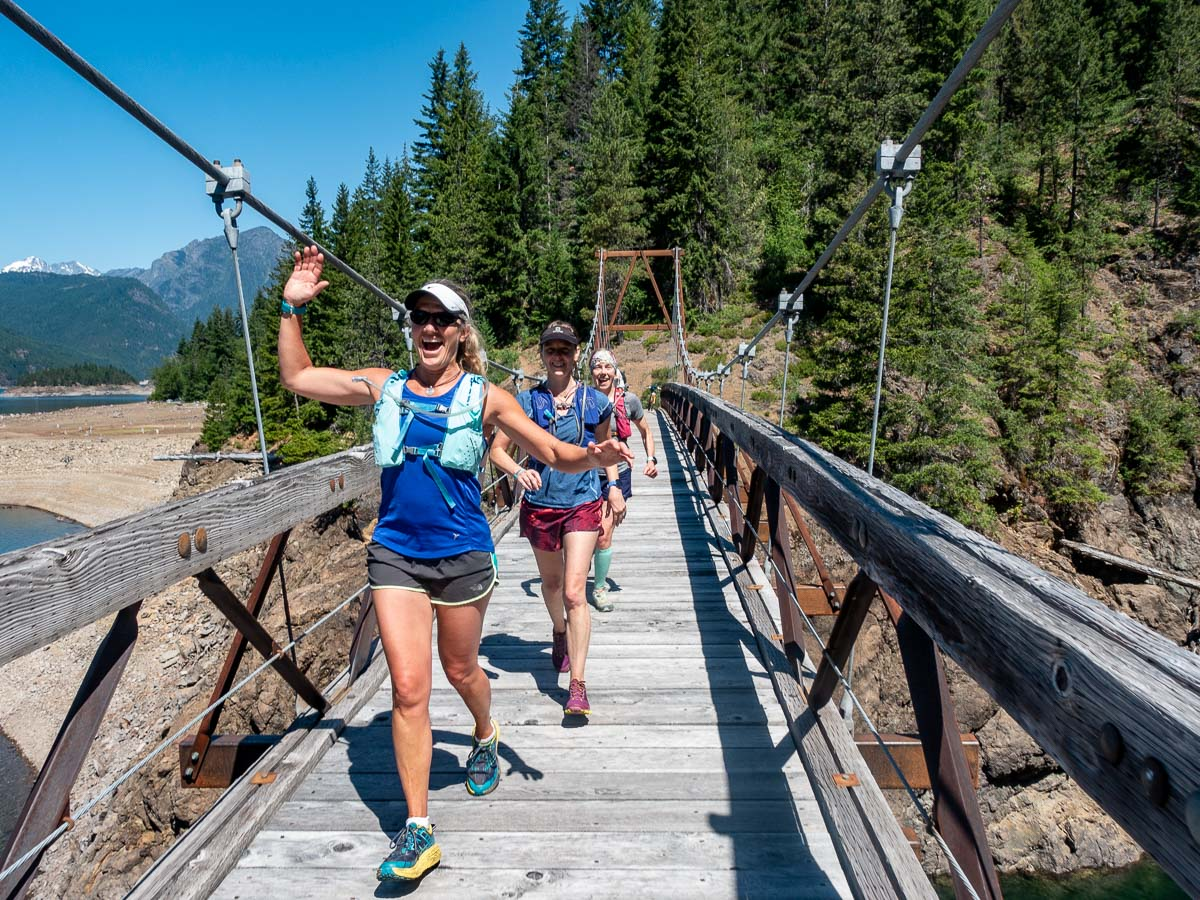 trail runners cross a suspension bridge