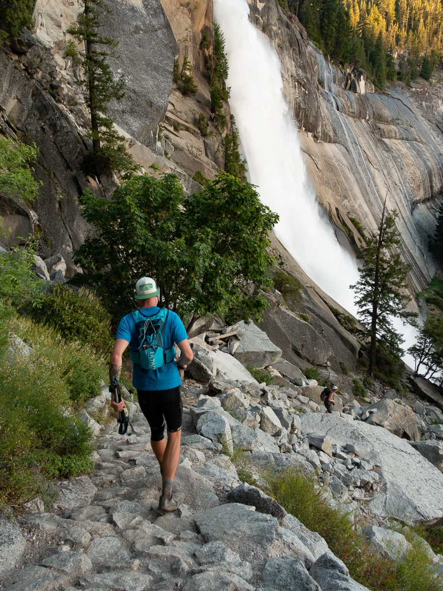a man running down a rocky trail with a waterfall in the background.