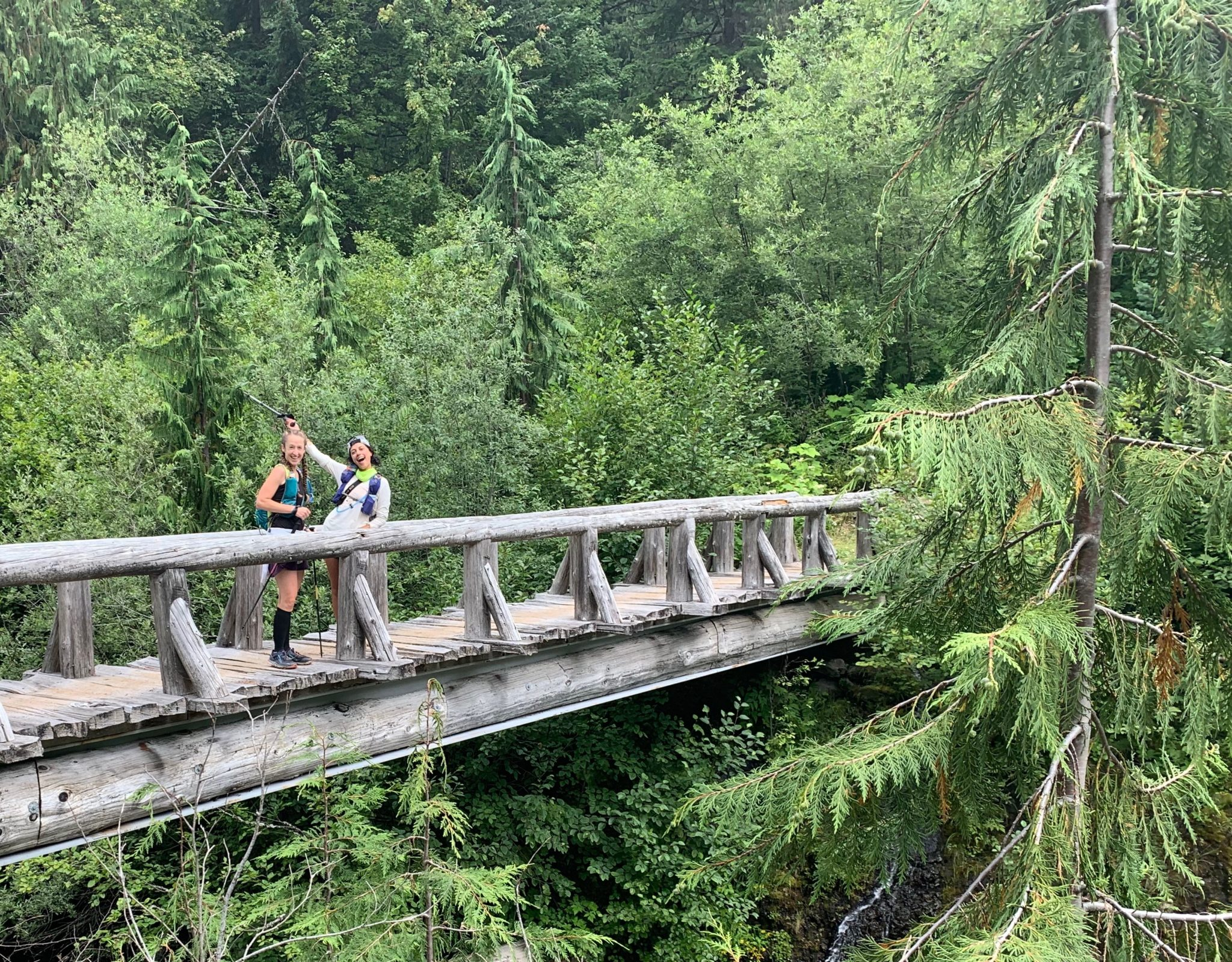 two trail runners crossing a bridge in Mt. Rainier National Park
