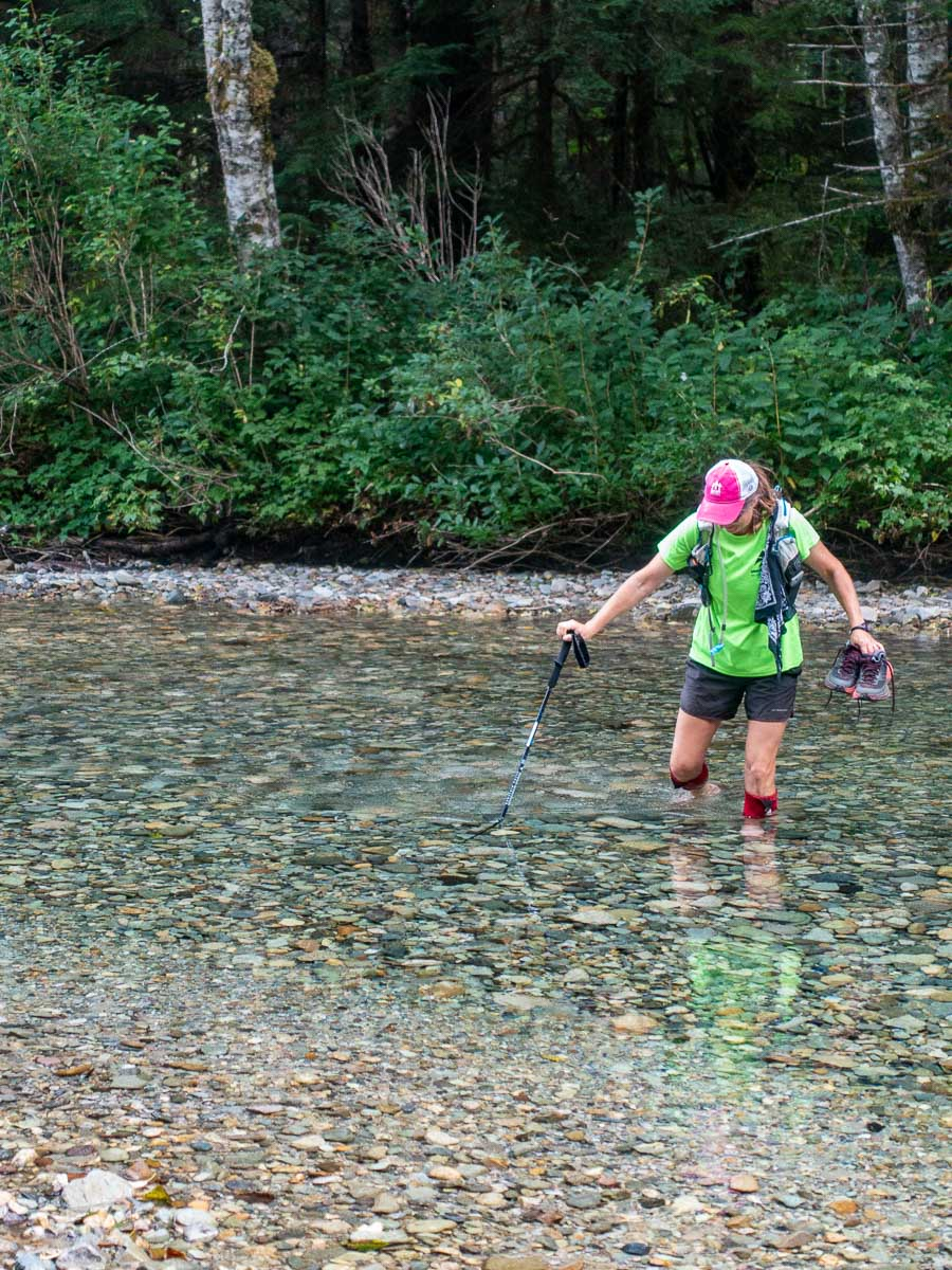 a trail runner fords a river