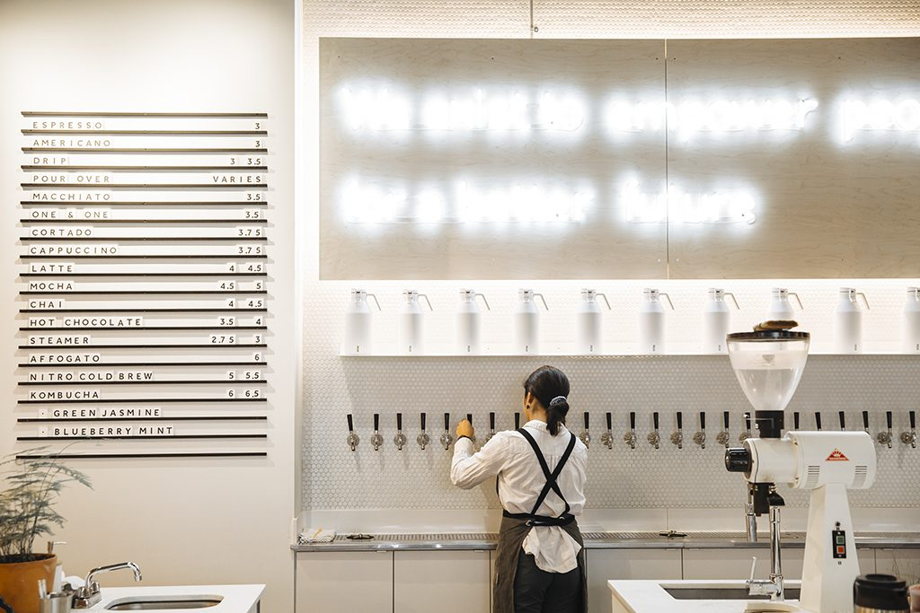 A woman pouring coffee from a wall of coffee taps